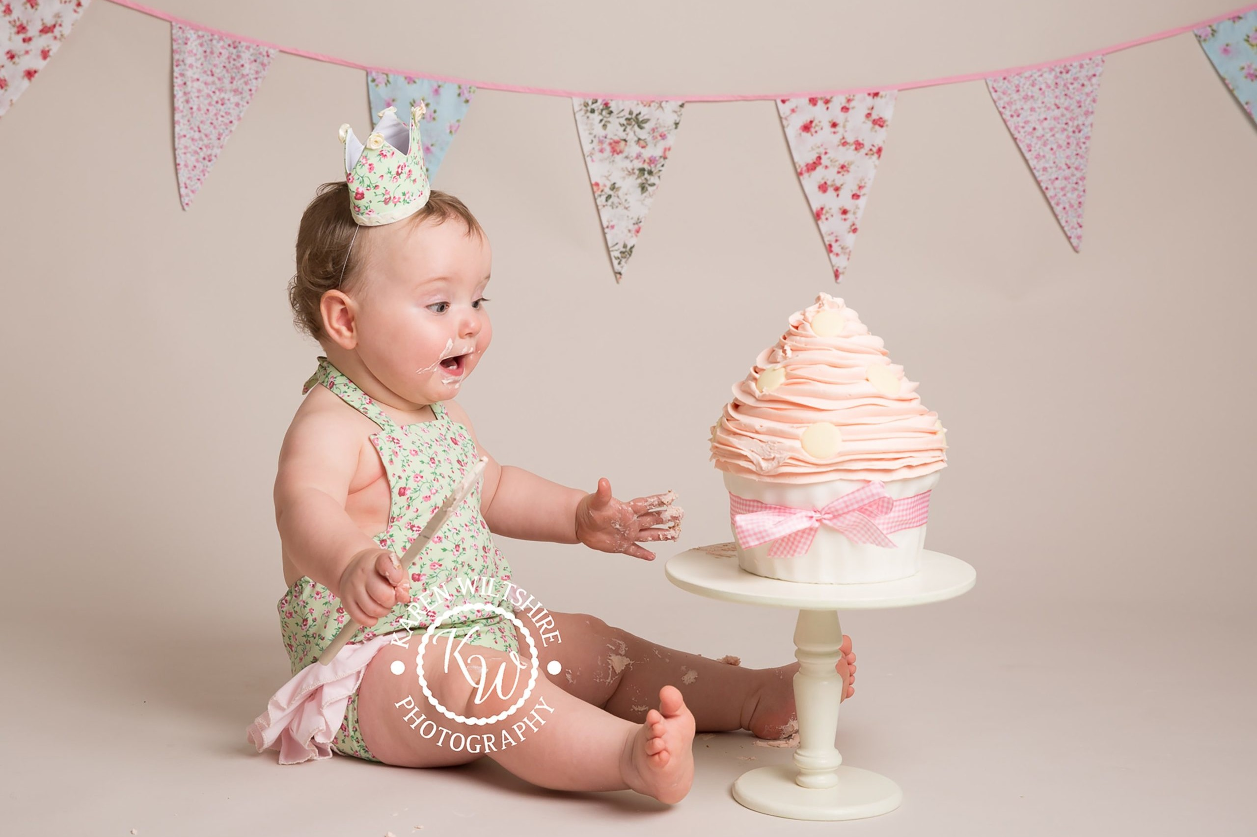 excited baby girl about to tuck into a giant pink cake