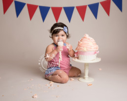 Baby girl sitting with a giant cupcake ready to eat it