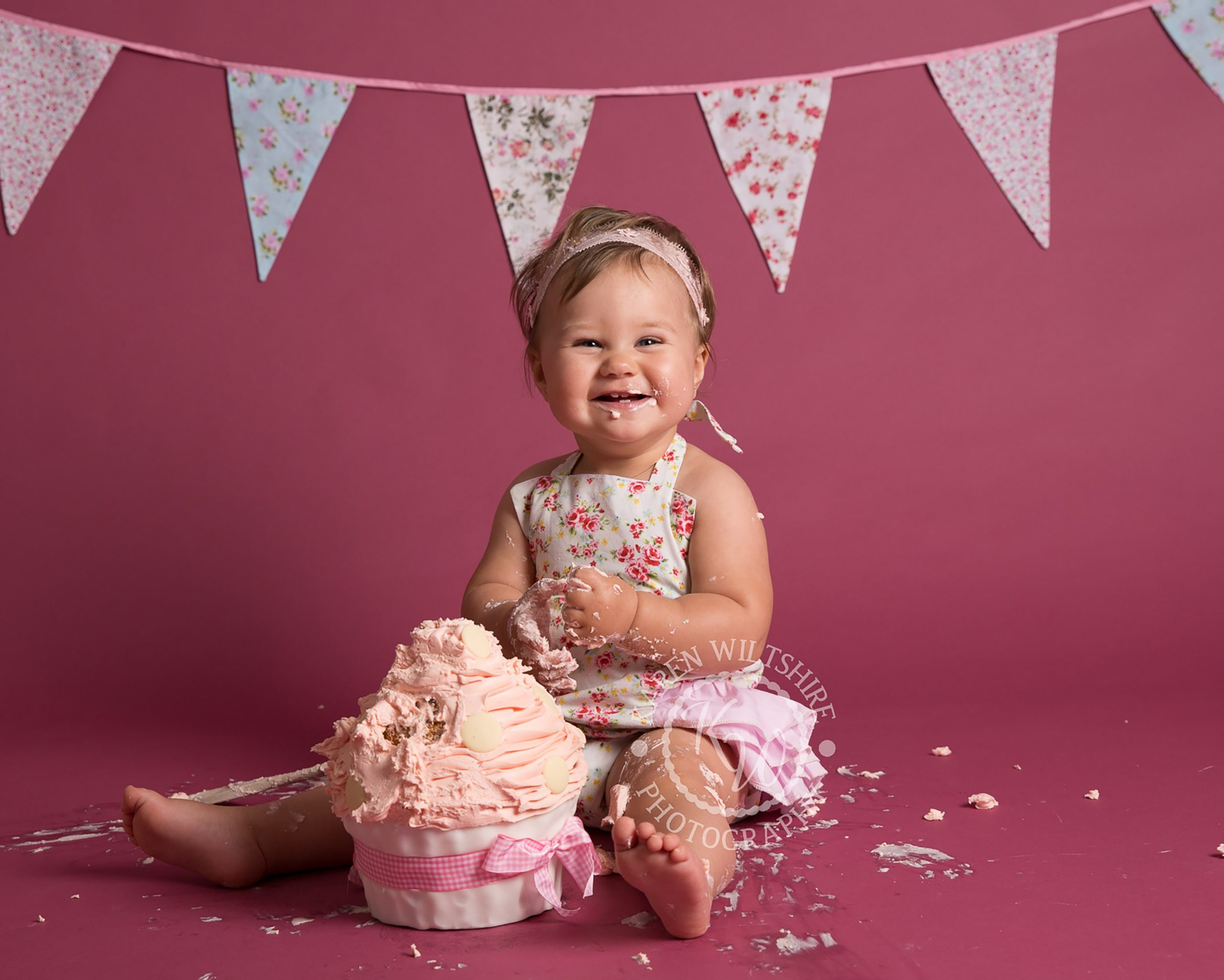 Happy baby girl with cake covered hands and face