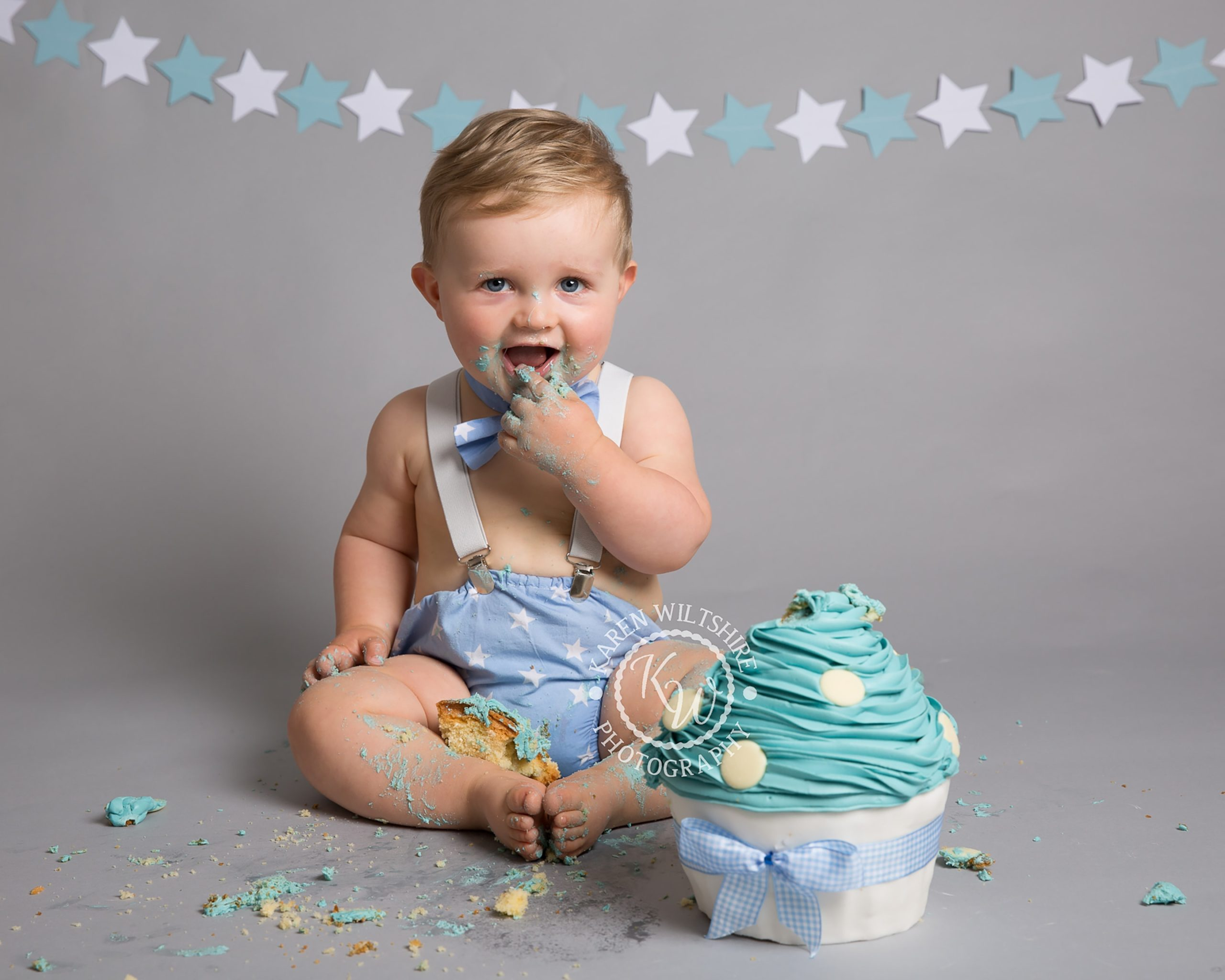 baby boy in blue outfit enjoying a large cupcake
