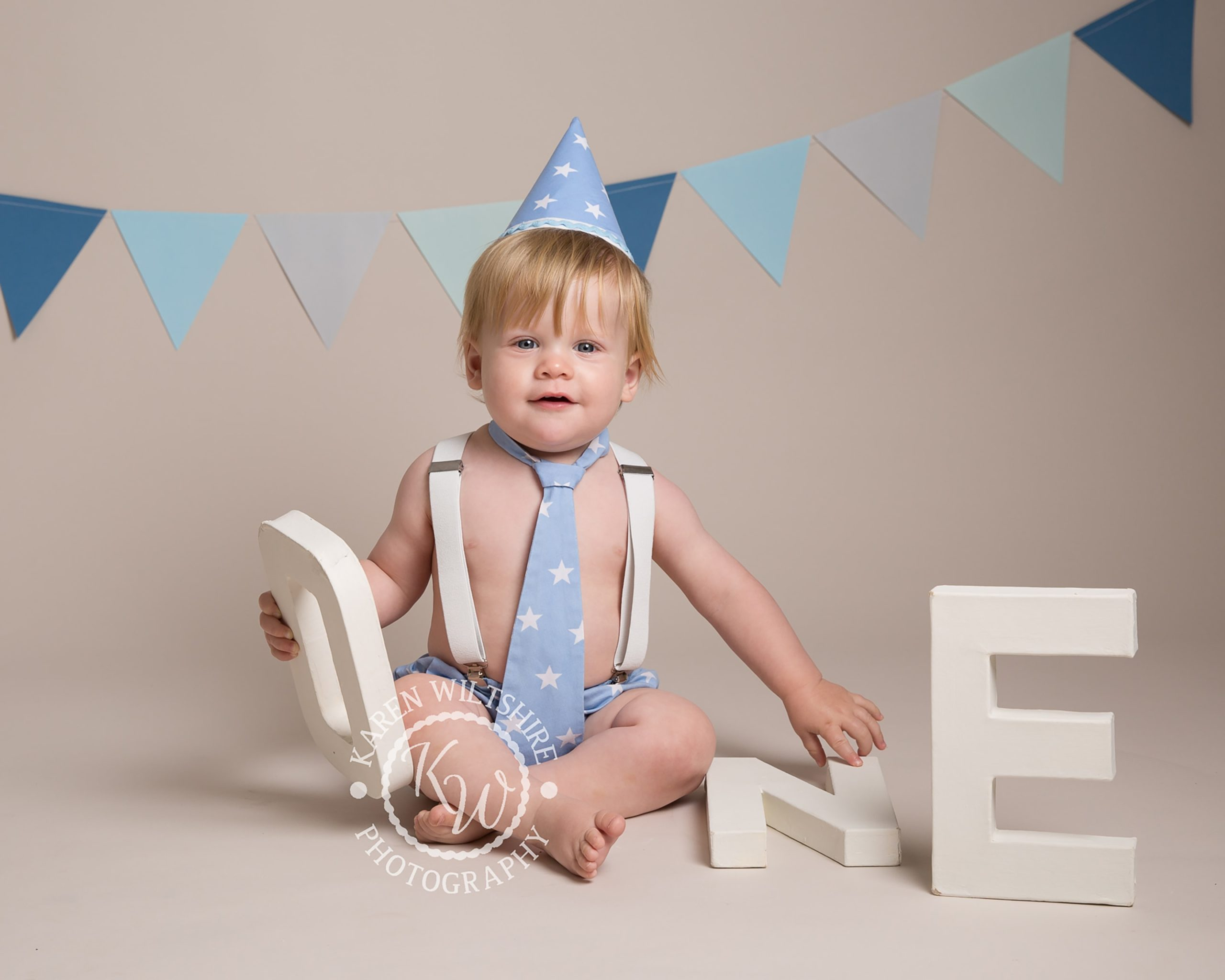 baby in blue star tie and pants