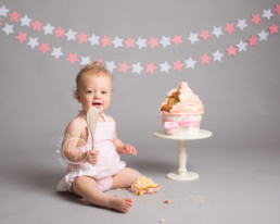one year old baby girl eating giant cupcake