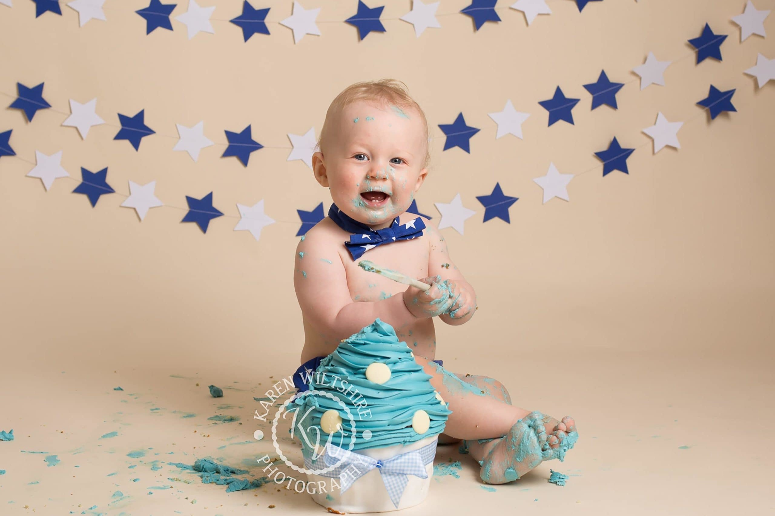 Baby boy enjoying a first birthday photoshoot with a large cupcake to smash