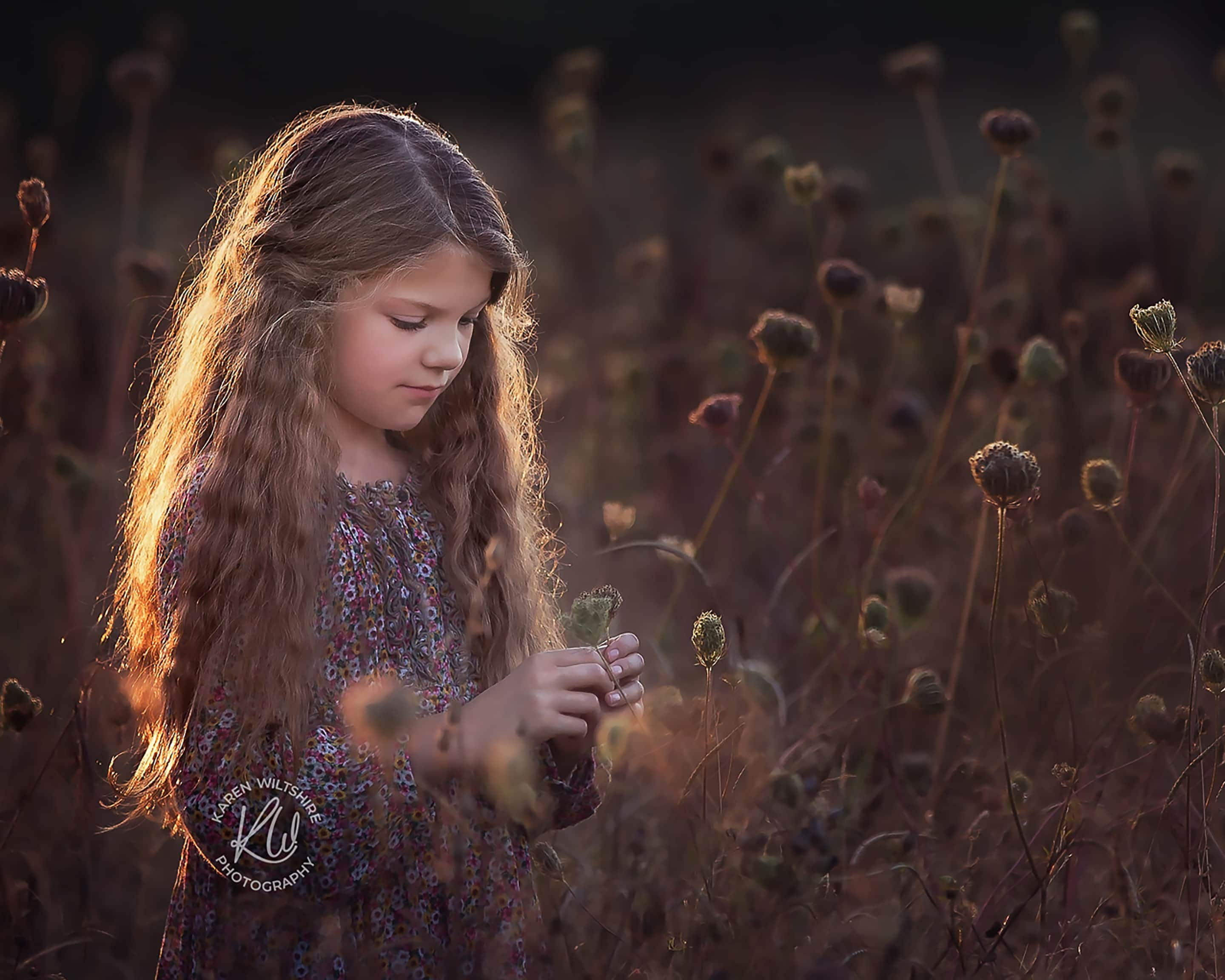 Long haired girl in field of seed heads