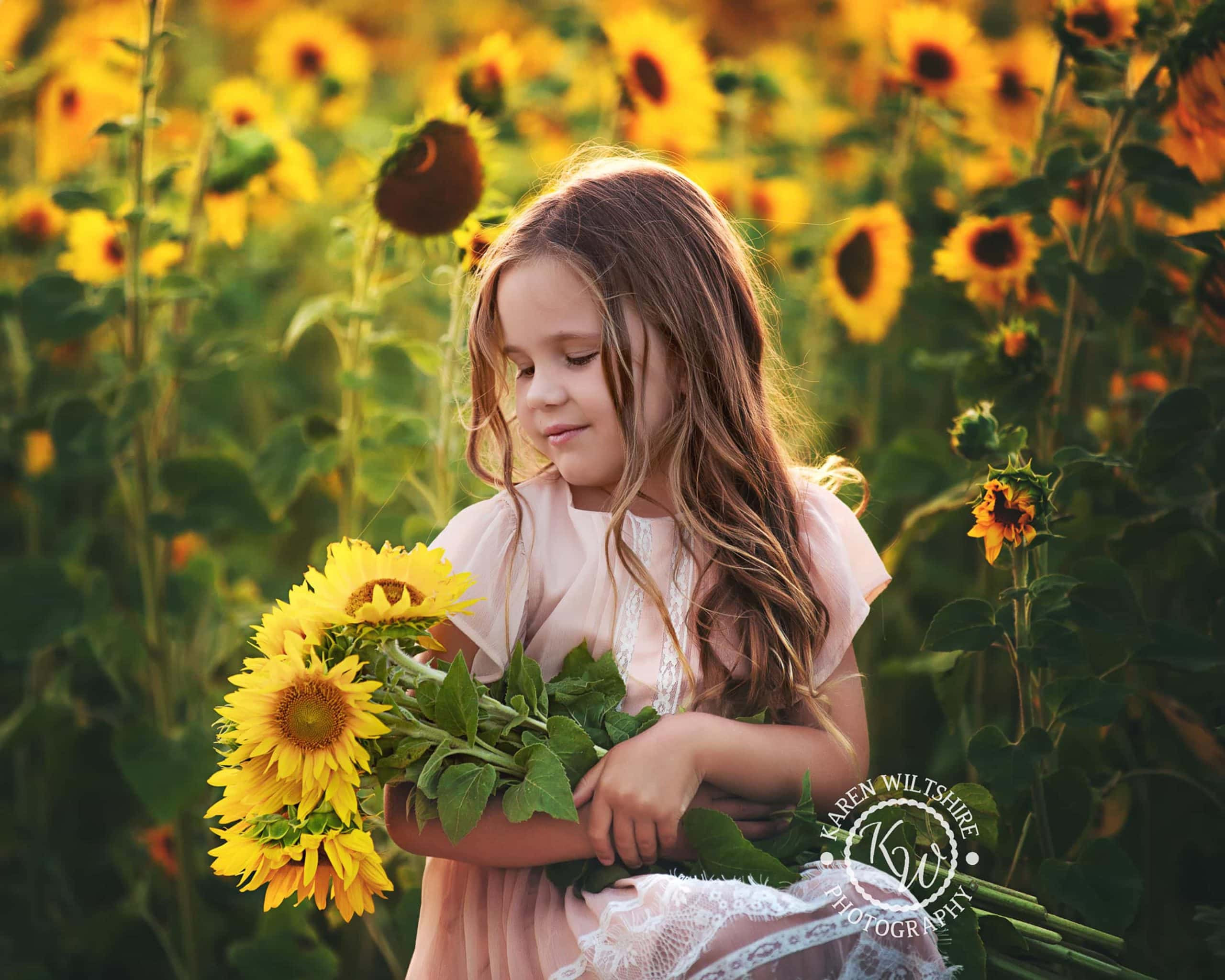 Young girl holding a large bunch of sunflowers