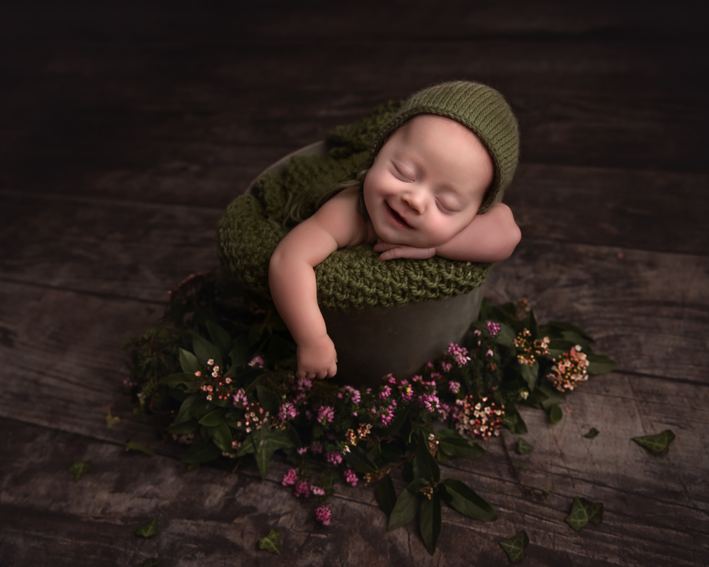 Newborn baby smiling whilst posed in a metal bucket with flowers