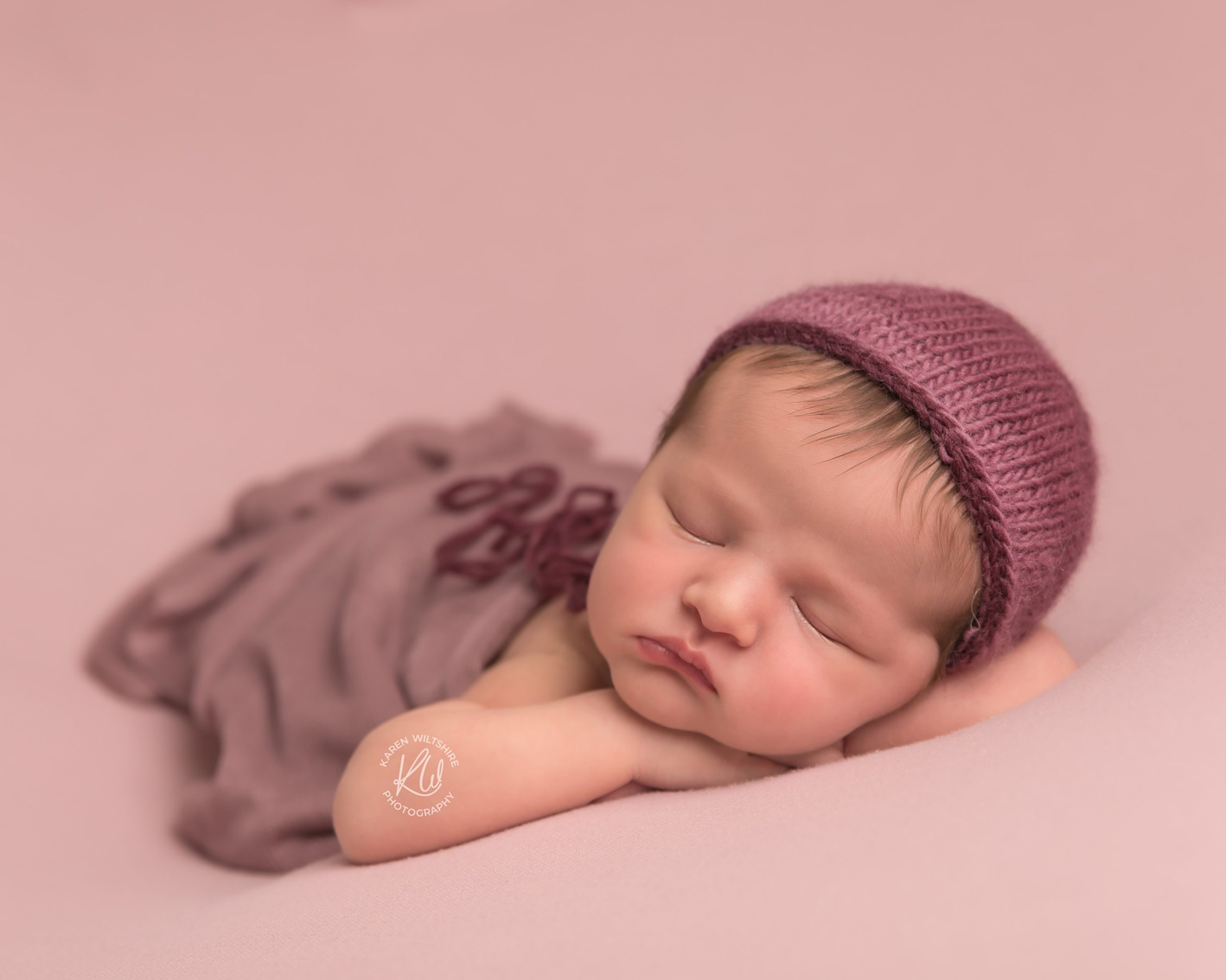 Baby girl sleeping soundly in a pink bonnet and blanket