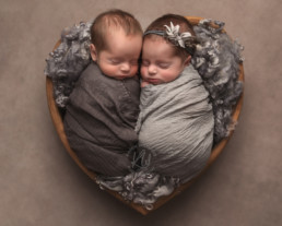 Boy and girl baby twins wrapped together sleeping
