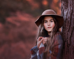 Young girl in hat leaning against a tree in autumn