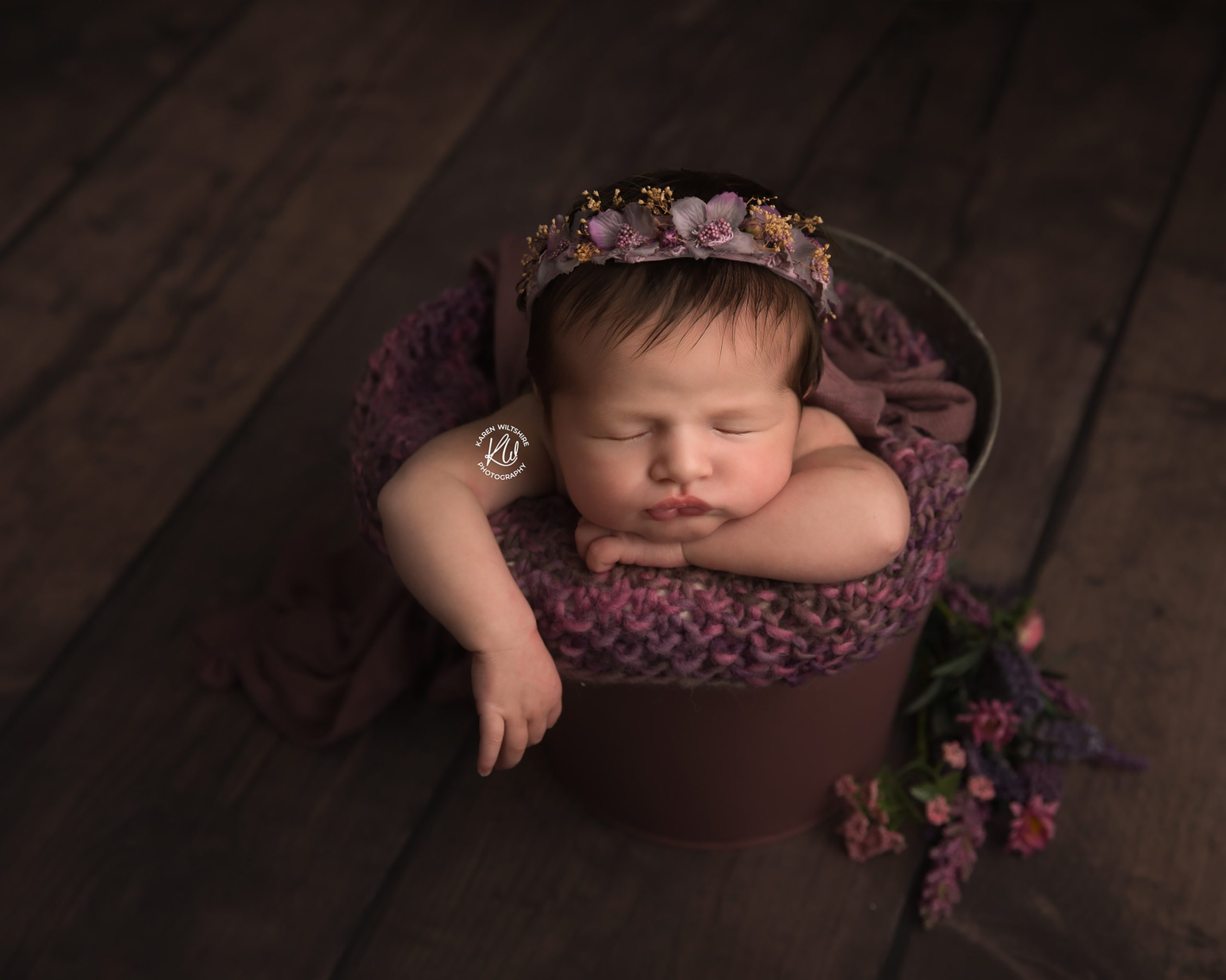 Baby girl sleeping in a bucket posed with flowers