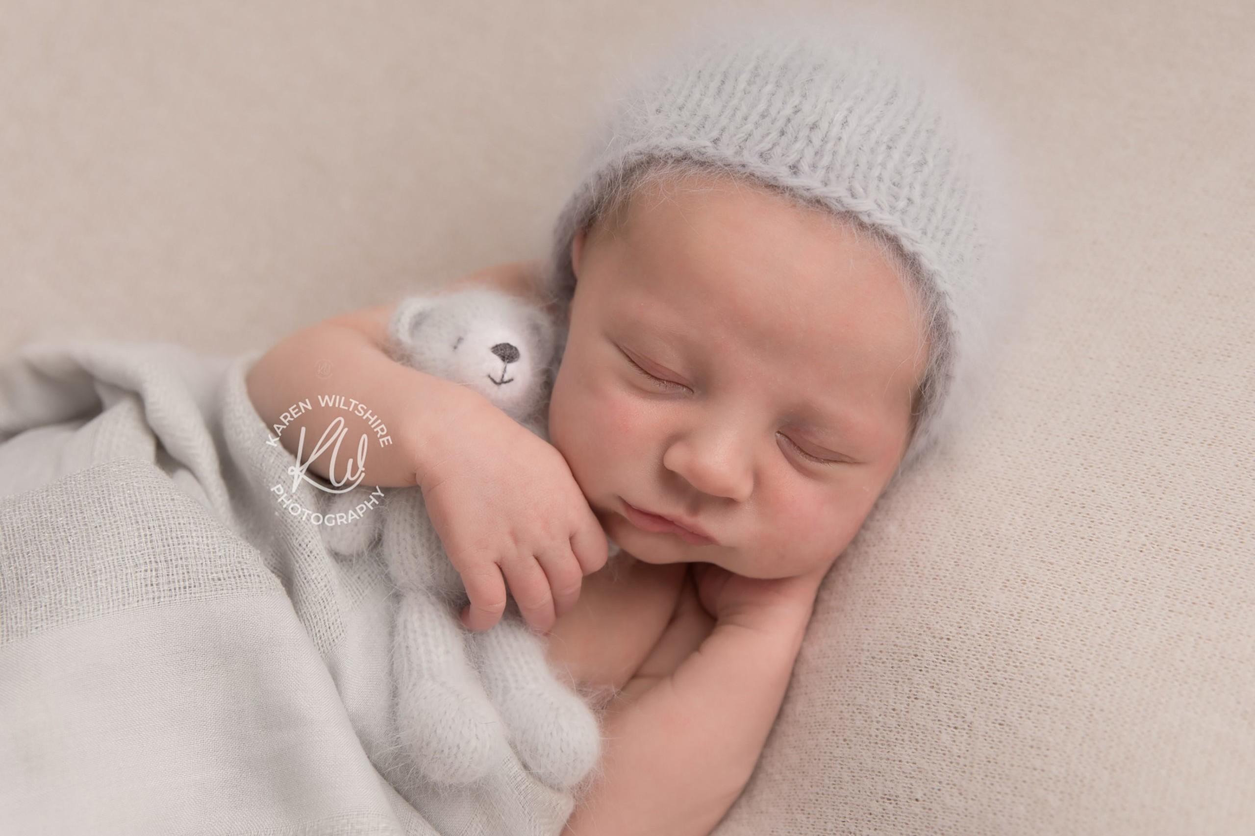 Baby in grey hat cuddling a grey fluffy teddy bear