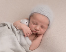 Baby in grey hat cuddling a grey fluffy teddy bear