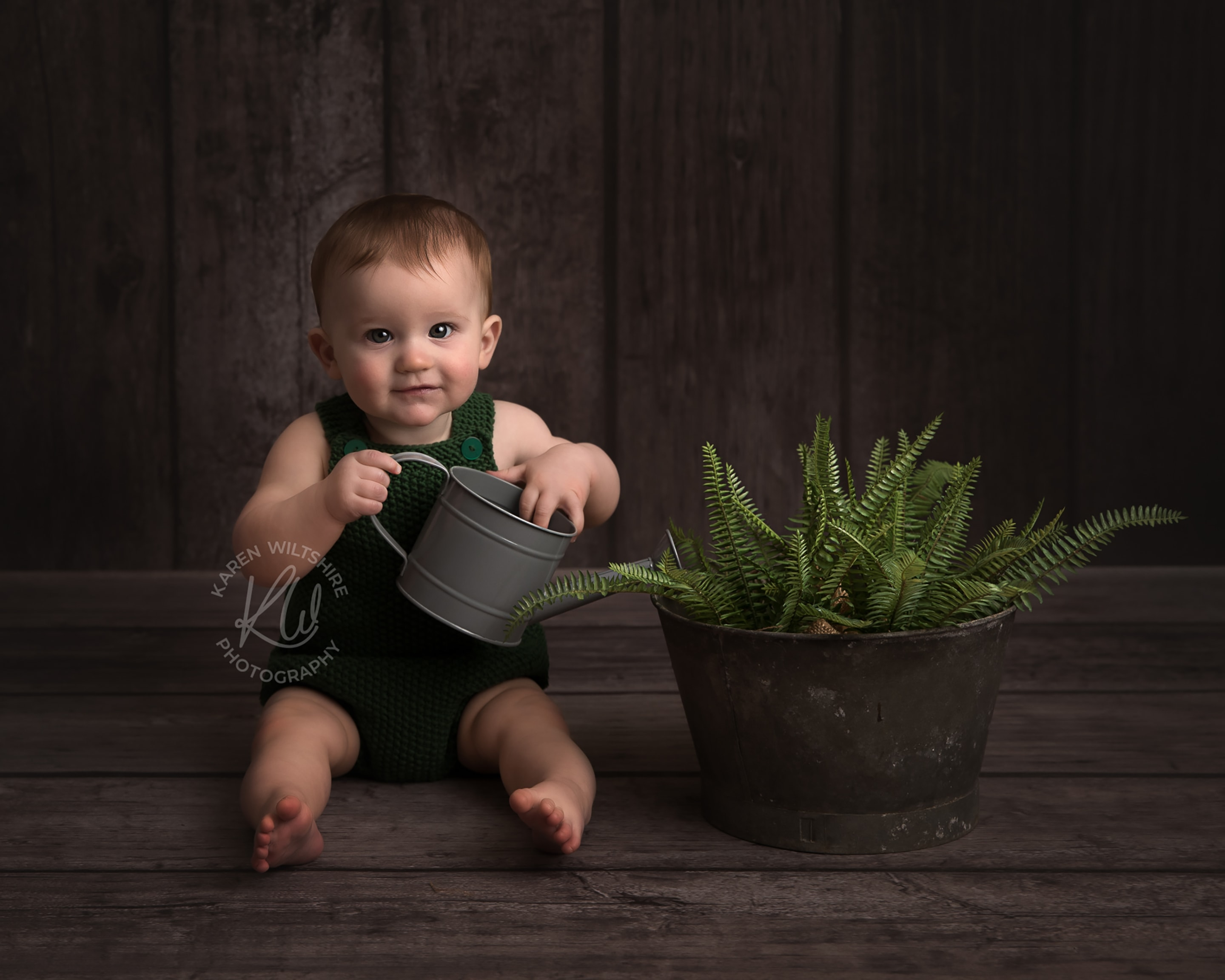 Baby boy watering plants with miniature watering can